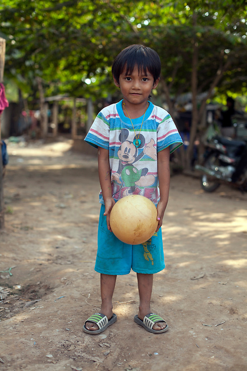 Portrait of a young boy with a ball in a small village outside of Phnom Penh, Cambodia. <br /> <br /> Photos &copy; Dennis Drenner 2013.