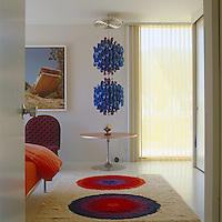 View into the master bedroom with a large modern rug and Verner Panton pendant light