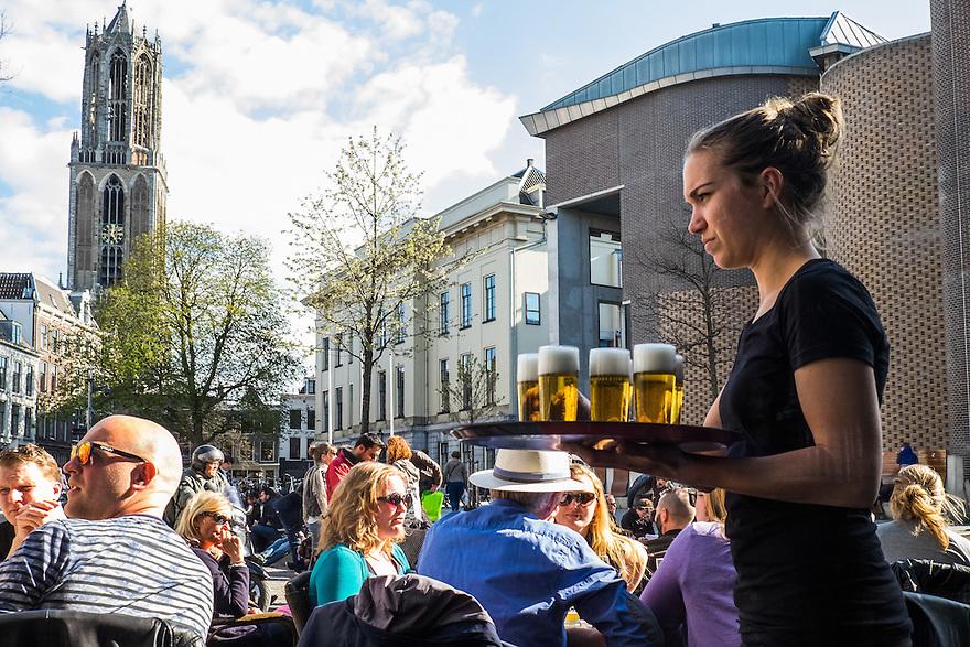 Nederland, Utrecht, 18 april 2015<br /> Serveerster brengt een blad vol bier naar klanten op het terras. De Dom van Utrecht op de achtergrond. <br /> Foto: Michiel Wijnbergh