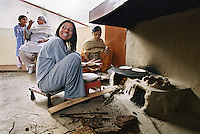 Women cook roti the traditional way on a tandoor built outside the modern kitchen of a Sikh family who divide their time between their homes in the UK and Jalandhar.