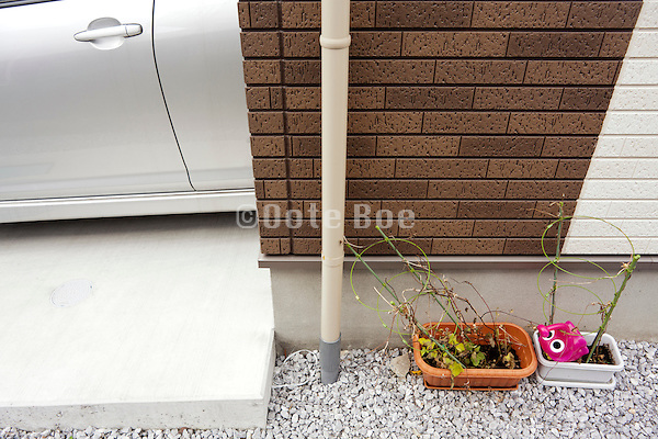 family home detail with car and dead potted plants Japan