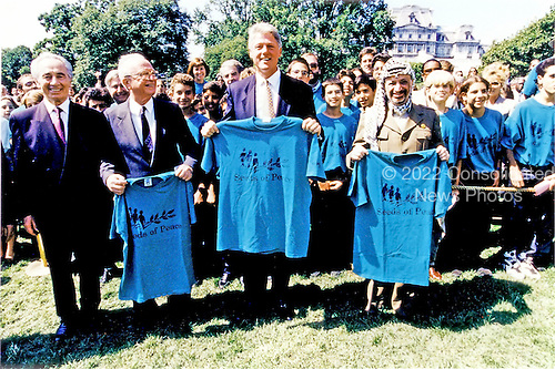 """Israeli Foreign Minister Shimon Peres, left, Israeli Prime Minister Yitzhak Rabin, left center, United States President Bill Clinton, center, and Palestine Liberation Organization Chairman Yasser Arafat, right, pose holding t-shirts of """"Seeds of Peace"""" after they signed the Oslo 1 Accords on the South Lawn of theWhite House on September 13, 1993.  The 47 """"Seeds of Peace"""" boys came from Israel, Egypt, and the Palestinian Territories and were the honored guests for the signing ceremony.  John Wallach, President and Founder of """"Seeds of Peace"""" can be seen to the immediate left behind Prime Minister Rabin. .Mandatory Credit: Bob McNeely - White House via CNP"""