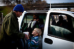 Six-year-old Ethan Paval, center, hands soup to SafeGround camper Jim Gilland, left, by the 12th Street bridge near the SafeGround camp in Sacramento, Calif., January 15, 2011.