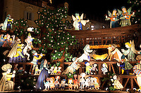 """Italy. Piedmont region. Turin. Setting for Emanuele Luzzati's evocative Nativity Scene on Piazza Castello. Illuminated nativity scene. A Nativity Scene, may be used to describe any depiction of the Nativity of Jesus in art, but in the sense covered here, also called a crib or in North America and France a crèche (meaning """"crib"""" or """"manger"""" in French). It means a three-dimensional folk art depiction of the birth or birthplace of Jesus, either sculpted or using two-dimensional (cut-out) figures arranged in a three-dimensional setting. Christian nativity scenes, in two dimensions (drawings, paintings, icons, etc.) or three (sculpture or other three-dimensional crafts), usually show Jesus in a manger, Joseph and Mary in a barn (or cave). Turin is the capital of the Piedmont region. 6.12.2011 © WHO /Didier Ruef"""
