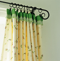 Curtains in a rosebud fabric trimmed with apple green gingham hang from a wrought iron curtain pole