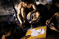 Textile workers play cards at a garment factory producing blue jeans. The factory, which specifically carries out a wear-and-tear process used to achieve a fashionable distressed look, produces approximately 10,000 pairs of jeans every day. Thousands of workers labour through the night scrubbing, spraying and tearing jeans in order to meet the production demand. The factory is owned by Huang Dehong, who left his impoverished village and arrived penniless in Zhongshan twenty years ago. China, the &quot;factory of the world&quot;, is now one of the world's largest producers of jeans and its textile workers are among the 200 million migrant labourers criss-crossing the country looking for a better life.