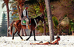 A girl sunbathes on the beach as a horse and rider trots past at Hua Hin, Thailand.