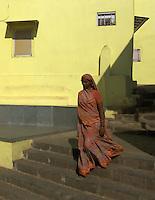 Mumbai, Banganga area women walking past a small Hindu temple