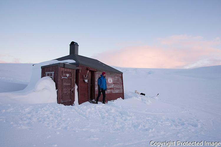 Mann foran hytta Heimdal på Varangerhalvøya. ---- Man in front of the cabin Heimdal on Varangerhalvøya.