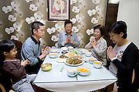"""La famille Quan réunie autour du patriarche Quan Husheng, prie au petit déjeuner, à Yanji, province de Jilin, en Chine, le 9 septembre 2009. De gauche à droite : Shen Xuanwu, 5 ans, de son nom catholique """"Gregoire"""", Shen Dongzhi """"Yohan"""" son père et le gendre de Quan Husheng, Quan Husheng """"Benedicto"""", Li Lisu """"Monica"""" sa femme, Quan Wuji """"Josée-Marie"""" leur fille et la mère de Shen Xuanwu. Photo par Lucas Schifres/Pictobank"""
