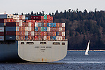 A sailboat is dwarfed byCargo Tankers as they lie in wait  to be offloaded as disagreements between the International Longshore & Warehouse Union (ILWU) and the Pacific Northwest ports over union contracts have resulted in work slowdowns in the loading and unloading of cargo at the Ports of Tacoma and Seattle since November 2014.  Arriving cargo container ships are beginning to stack up are being moored over in Manchester Bay near the Kitsap Peninsula on February 17, 2015. ©2015 Jim Bryant Photo. All RIghts Reserved