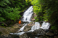 A hiker pauses to admire the Beaver Brook Cascades along the Appalachian Trail in Kinsman Notch, New Hampshire on the northern slopes of Mount Moosilauke.