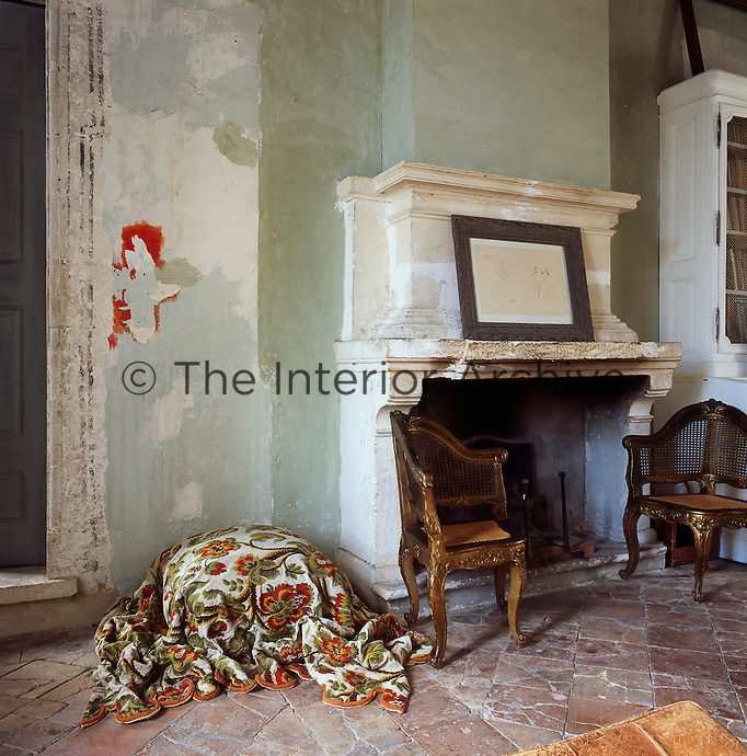 A detail of a bedroom with a stone fireplace and a terracotta tiled floor. The stone walls are painted with natural pigments inspired by the colours of Provence, while being careful to leave the original underlying layers, which gives the room an air of faded grandeur