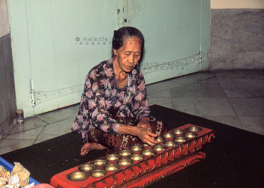 a woman with congklak (Indonesian game).<br /> una donna con il congklak  (gioco indonesiano)