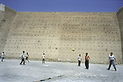 Children play football outside the 300 year old walls of 'The Ark', the oldest structure in town and once the home of the Emir of Bukhara, in the Old Silk Road trading route city of Bukhara, Uzbekistan