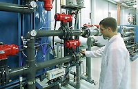 A technician inspects a water purification system.