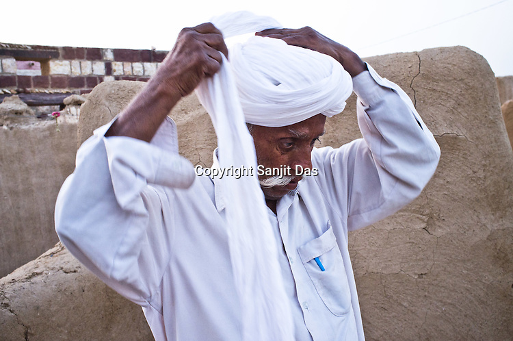 66-year-old Manganiyar artist, Lakha Khan ties his turban while getting ready for a portrait outside his house in Raneri village of Jodhpur district in Rajasthan, India. Photo: Sanjit Das/Panos