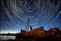 BNPS.co.uk (01202 558833).Pic: SamanthaCrimmin/BNPS..***Please Use Full Byline***..Star trails above rusty old steam ships in South Georgia...A British Doctors braved freezing conditions to capture unique pictures of the night sky from the tiny British island of South Georgia in the remote South Atlantic...Amateur photographer Samantha Crimmin's stunning photos of the sky at night over South Georgia have left locals so star-struck they have been turned into stamps...Dr Samantha Crimmin was working as an emergency medic for the British Antartic Survey team when she took the celestial images in her spare time...Dr Crimmin used long exposures and plenty of patience to create the incredible shots that show star trails in a perfect circular motion...Her gallery of photos depict the night sky above different locations on the tiny outpost in the south Atlantic...They include one above the Harker Glacier - named after British geologist Alfred Harker - and over the wrecks of two Norwegian whaling ships at Grytviken.