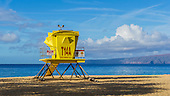 A yellow lifeguard station with warning signs at a beach on Maui.