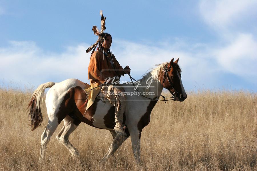 A Native American Indian man on horseback riding the prairie of South Dakota