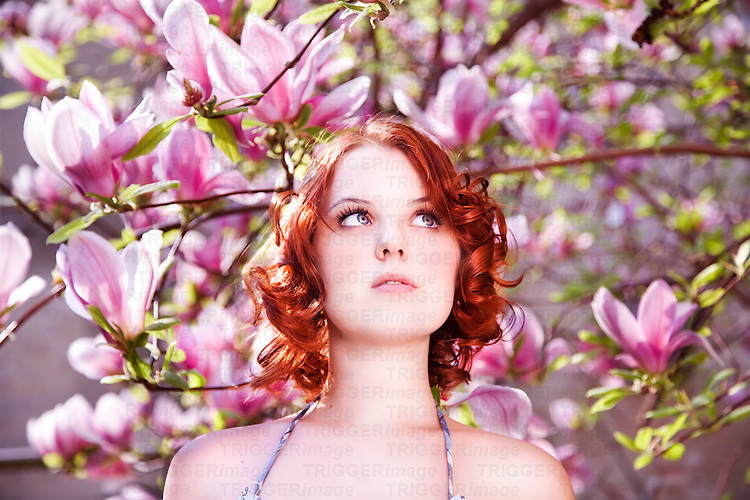 Redheaded young female looking up in front of pink magnolias