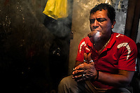A Salvadorean 'brujo' (sorcerer) calls the supernatural entities to help him to predict the future from burn tobacco leaves in a street fortune telling shop in San Salvador, El Salvador, 18 February 2014. Due to the strong historical tradition of using tobacco by indigenous shamen in Americas, nowadays, the reading of tobacco is one of the most most widespread methods of divination, employed by esoteric practitioners and healers in all Latin American countries. According to the shapes of burn leaves, colors of ash and smoke, burning velocity and other factors, the experienced fortune teller interprets the manifested signs in relation with the supposed future of people involved in the tobacco ritual.
