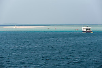 Devana Kandu, Finolu Island, Felidhoo Atoll, Maldives; a view of the small sandbar island of Finolu with people walking through the shallow water to get back to the boat