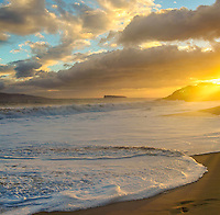 The setting sun casts its light over Big Beach at Makena State Park on Maui.
