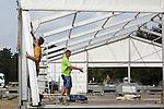 Foto: VidiPhoto<br /> <br /> NIJMEGEN - Met man en macht wordt maandag gewerkt aan de opbouw van het grootste asielzoekerscentrum van Nederland: de noodopvang Heumensoord bij Nijmegen. Op de plek waar tijdens de Vierdaagse zon 5500 militairen worden gelegerd, komen eind deze week de eerste 800 asielzoekers aan. Uiteindelijk zullen dat er 3000 worden. Het gaat volgens de gemeente om een tijdelijke opvang tot juni volgend jaar. Daarna komt het natuurgebied weer beschikbaar voor de Vierdaagse. Maandag was het de drukste dag. Behalve dat al het materiaal werd aangevoerd, werden ook de eerste paviljoens geplaatst. Volgens aannemer Weijers Grond-, Water- en Wegenbouw BV uit Nijmegen gaat het om een unieke klus die onder grote tijdsdruk geklaard moet worden. Het Centraal Orgaan opvang Asielzoekers (COA) heeft het terrein inmiddels hermetisch afgesloten om pottenkijkers te weren. Het is niet voor het eerst dat op Heumensoord een tijdelijke noodopvang voor asielzoekers komt. In 1990 verbleven er zo'n 300 asielzoekers. Zij kregen direct na de Vierdaagse onderdak in het Vierdaagsekamp. 8 jaar later, in 1998, werd er ook een noodkamp gevestigd. Destijds werd op Heumensoord huisvesting geregeld voor een kleine 1.000 asielzoekers.