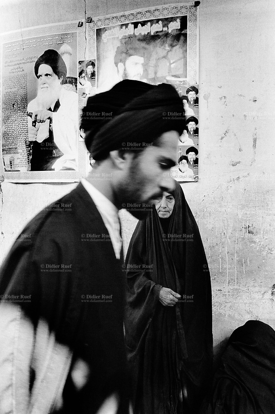 Iraq. Najaf. A mullah walks by a group of women waiting near the house of the young shiite leader Moktada Al Sadr. Two pictures are taped on the wall. The first on the left is of the shiite spritual leader Mohammed Al Sadr, killed by the Saddam Hussein regime. The second on the right is of Moktada Al Sadr who is the son of Mohammed Al Sadr. The women wear the abaya and the hijab on their heads to cover their hair. The abaya, sometimes also called aba, is a simple, loose over-garment, essentially a robe-like dress, worn by some women in parts of the Islamic world. Traditional abaya are black and may be either a large square of fabric draped from the shoulders or head or a long caftan. The abaya covers the whole body except the face, feet, and hands. The word hijab (or hidjab) refers to both the veil covering the head and traditionally worn by muslim women (Islamic headscarf), but also the  modest muslim styles of dress in general. The mullah is generally used to refer to a Muslim man, educated in Islamic theology and sacred law. The title, given to some Islamic clergy, is the name commonly given to local Islamic clerics or mosque leaders. 26.02.04 © 2004 Didier Ruef .