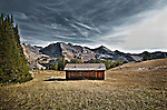 Pioneer Cabin near Sun Valley Idaho with the Pioneer Mountain Range in the back ground. Taken at mid-day in the late fall,  Sign on roof reads: &quot;The higher you get, the higher you get&quot;  This cabin was built by the Sun Valley Company as a back country ski hut.
