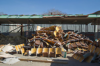 pile of discarded chairs at a dump