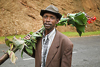Rwanda. Western province. Village of Utarare Wa Ndaba. Hutu man carries flowers on his right shoulder. Concrete road. © 2007 Didier Ruef