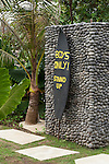 Komune Resort & Beach Club, Bali, Indonesia; a surf board marks the entrance to the mens restroom near the beach