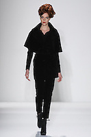Model walks runway in a black cotton corduroy capelet-trench jacket w/attached baby corduroy shirt, and black cotton corduroy skinny pant, from the Zang Toi Fall 2012 &quot;Glamour At Gstaad&quot; collection, during Mercedes-Benz Fashion Week New York Fall 2012 at Lincoln Center.