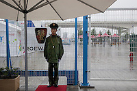 China. Shanghai. World Expo. Expo 2010 Shanghai China. A policeman on guard stands at the door's entrance to the Expo. A large beige umbrella is sheltering him from the rain. Cloudy sky. 25.06.10 © 2010 Didier Ruef