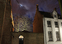 BRUGES, BELGIUM - FEBRUARY 07 : A low angle view of a Beguine's house with a sparkling moon in a cloudy sky on February 07, 2009 in Bruges, Western Flanders, Belgium. The 'Beguinage of the Vineyard' was founded in the first half of the 13th century during the reign of Margaret of Constantinople. (Photo by Manuel Cohen)