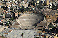 Roman Theatre, downtown Amman, Jordan. Built during the reign of Antonius Pius (138-161AD), the large and steeply raked theatre could seat 6000 people and is divided into 3 tiers. It is built into the hillside, oriented north to keep the sun off the spectators and was restored in 1957. View from above with cityscape of downtown Amman in the background. Picture by Manuel Cohen
