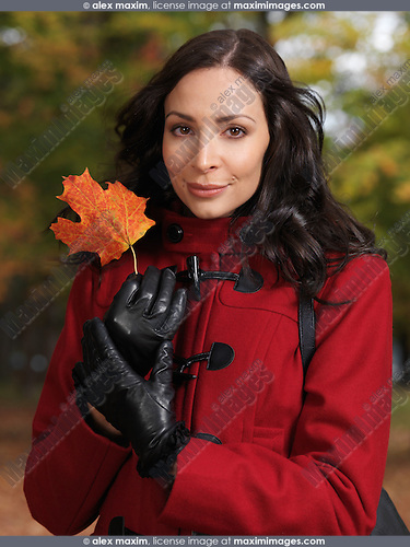 Portrait of a beautiful woman holding a red maple leaf in her hands