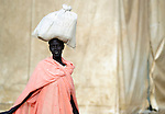 A displaced woman carries a bag on her head in Agok, a town in the contested Abyei region where tens of thousands of people fled in 2011 after an attack by soldiers and militias from the northern Republic of Sudan on most parts of Abyei. Although the 2005 Comprehensive Peace Agreement called for residents of Abyei--which sits on the border between Sudan and South Sudan--to hold a referendum on whether they wanted to align with the north or the newly independent South Sudan, the government in Khartoum and northern-backed Misseriya nomads, excluded from voting as they only live part of the year in Abyei, blocked the vote and attacked the majority Dinka Ngok population. The African Union has proposed a new peace plan, including a referendum to be held in October 2013, but it has been rejected by the Misseriya and Khartoum. The Catholic parish of Abyei, with support from Caritas South Sudan and other international church partners, has maintained its pastoral presence among the displaced and assisted them with food, shelter, and other relief supplies.