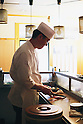 "Tokyo, Japan - Japanese Sushi Chef, Nogami Shinji slices raw fish with his very sharp knife : Japanese Sushi Chef, Nogami Shinji, established his own Sushi restaurant in 2001 called ""Nogami"" in the Hacchobori district of Tokyo. He started his career 25 years ago and continues to master the culinary craft to make the perfect sushi. His father, also a sushi chef, and his son who is currently in training to become a sushi chef shows illustrate how the art of making sushi has been passed down through generations. Nogami's day begins in the very early morning hours when he selects fish at the Tsukiji market. Choosing the best fish is considered the most important part of his work and he makes sure that he always has about 30 different varieties from which to serve. His restaurant is open late until 10pm and many regulars stay even later so Nogami will usually take an afternoon sleep break between 2pm-5pm when the restaurant is closed. ....Nogami-san's hobby is also fishing and he lives in the Tokyo Bay area so can do this in his free time. He usually releases what he catches though as he is worried that the Tokyo Bay water is not so clean. His son trains, works and sleeps at a different restaurant which is normal for a junior. As he improves his technique he will start to help more in his father's restaurant and eventually take over. There are no exams or text books for sushi chefs so this learning is all based on experience. Nogami's wife also helps out in the restaurant when she has time when their young daughter is at school.....Nogami often serves non-Japanese customers and he is surprised that ""They can eat anything and they often use heaps of wasabi"". He is proud of his ""Aritsugu"" knife which is worth about $700 and his most important tool. ....Nogami-san is worried that since the great March 11 earthquake and tsunami, the cost of fish has soared. (Photo by Yosuke Tanaka/AFLO)"