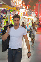 good looking twenty something year old man walking through a carnival in Atlantic City, New Jersey