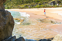 Young woman jumping on pristine Anapai Bay on Abel Tasman Coast Track, Abel Tasman National Park, Nelson Region, South Island, New Zealand