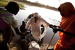 Women help an elderly man off of a ferry across the Kiir river.