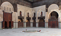 Low angle view of a corner of the central courtyard, Bou Inania Madrasa, Fez, Morocco, pictured on February 21, 2009 in the afternoon. The Bou Inania Madrasa was founded as a boarding school and mosque in AD 1351-56 by Abu Inan Faris, also the founder of the Bou Inania Madrasa in Meknes, and holds the status of Grand Mosque. A fine example of Marenid architecture with its intricate plasterwork, carved cedar and decorated tiles or zellij it is the only mosque in Fez open to non-Muslim visitors. It was renovated in the 18th and 20th centuries. Fez, Morocco's second largest city, and one of the four imperial cities, was founded in 789 by Idris I on the banks of the River Fez. The oldest university in the world is here and the city is still the Moroccan cultural and spiritual centre. Fez has three sectors: the oldest part, the walled city of Fes-el-Bali, houses Morocco's largest medina and is a UNESCO World Heritage Site;  Fes-el-Jedid was founded in 1244 as a new capital by the Merenid dynasty, and contains the Mellah, or Jewish quarter; Ville Nouvelle was built by the French who took over most of Morocco in 1912 and transferred the capital to Rabat. Picture by Manuel Cohen.