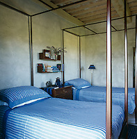 The guest bedroom has a pair of wooden framed beds with blue and white striped bed linen