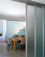 This dining room can be exposed or cut off from the adjacent kitchen by three glazed sliding panels that make up a screen wall