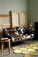 In this corner of the living room a cow-hide sofa serves as a partition to screen off a collection of stored paintings
