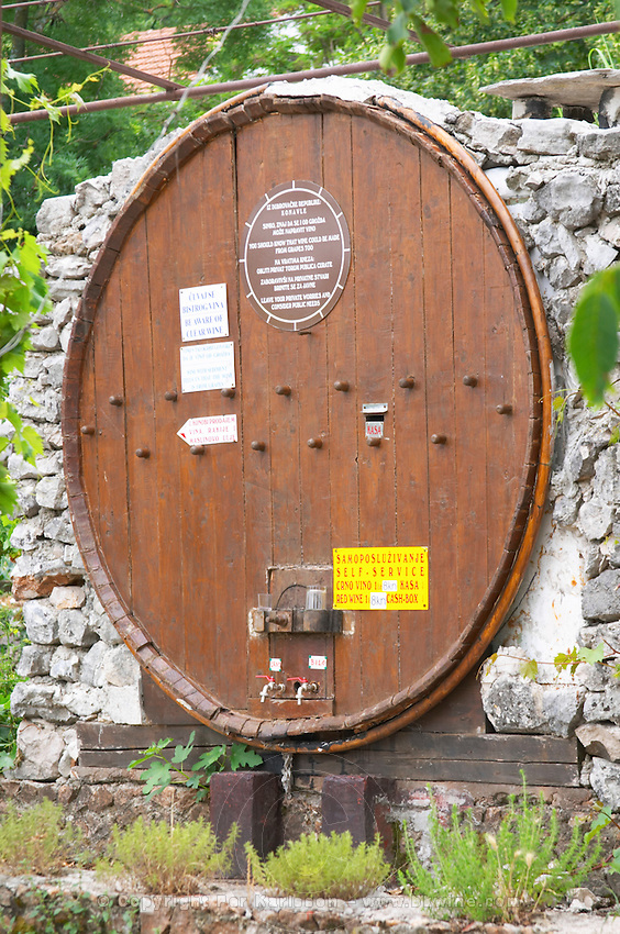 A big barrel at a winery for self service buying the wine. Two taps for red and white and a glass to taste. Potmje village, Dingac wine region, Peljesac peninsula. Dingac village and region. Peljesac peninsula. Dalmatian Coast, Croatia, Europe.