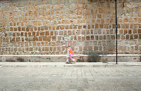 A woman in costume walks down the street outside the walls of the Etno-botanical gardens of the Santo Domingo convent, Oaxaca City, Oaxaca, Mexico